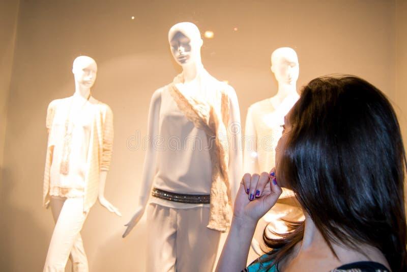 有站立在一家奢侈品商店前面和看新的收藏的黑发的美丽的女孩 免版税库存照片