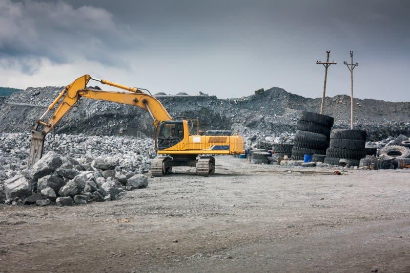 有站立在与岩石的小山的铁锹的重的挖掘机 免版税库存照片