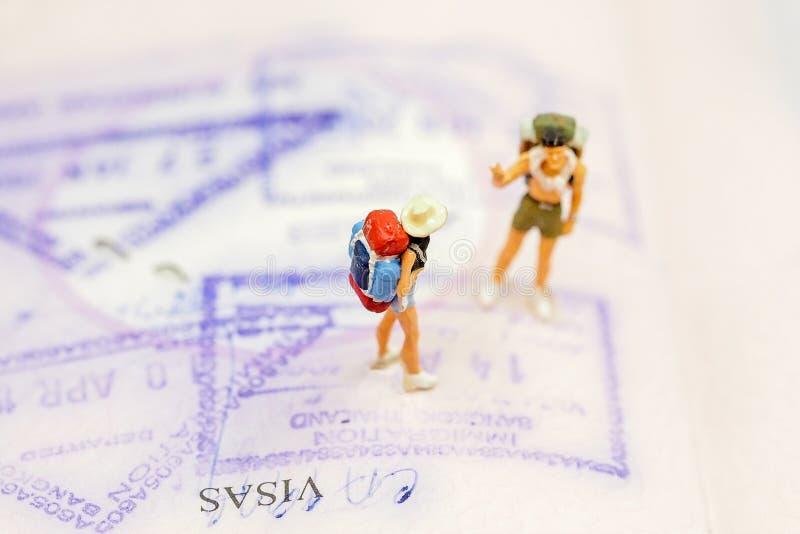 有站立在与拷贝空间的护照的背包的微型小组旅客旅行的环球 免版税图库摄影