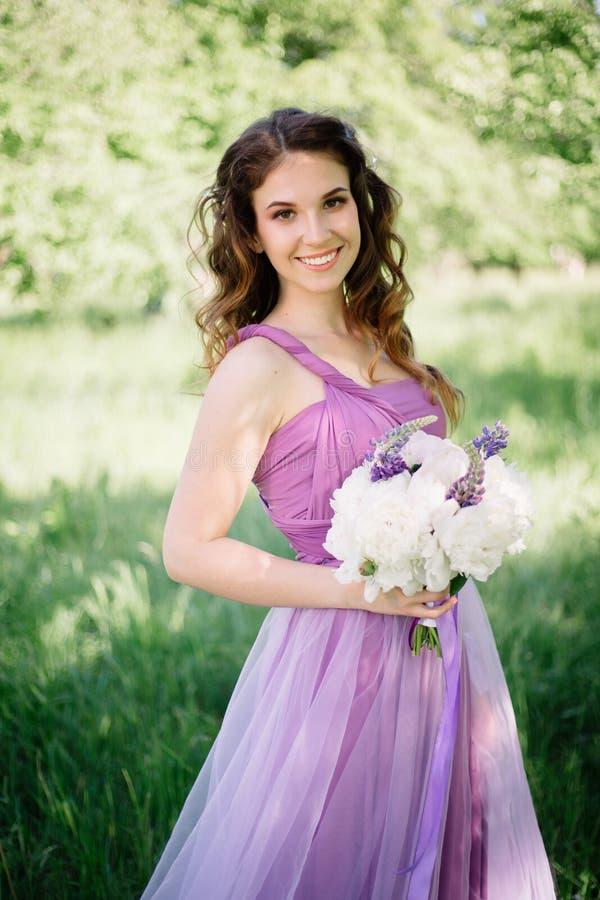 有站立在仪式的牡丹和其他花豪华五颜六色的婚礼花束的女傧相  库存照片