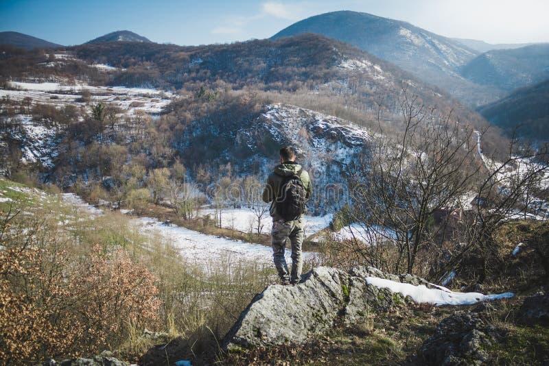 有站立在冬天山的峭壁顶部的背包的远足者 免版税库存图片