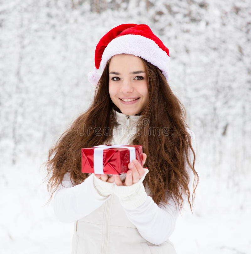 有站立在冬天森林里的圣诞老人帽子和小红色礼物盒的女孩 库存照片