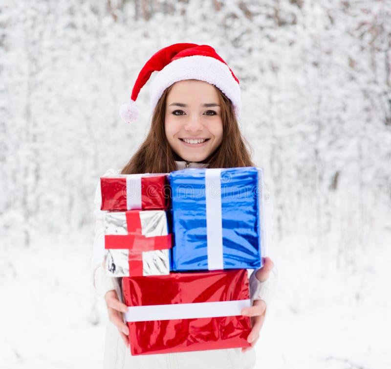 有站立在冬天森林里的圣诞老人帽子和红色礼物盒的青少年的女孩 库存图片