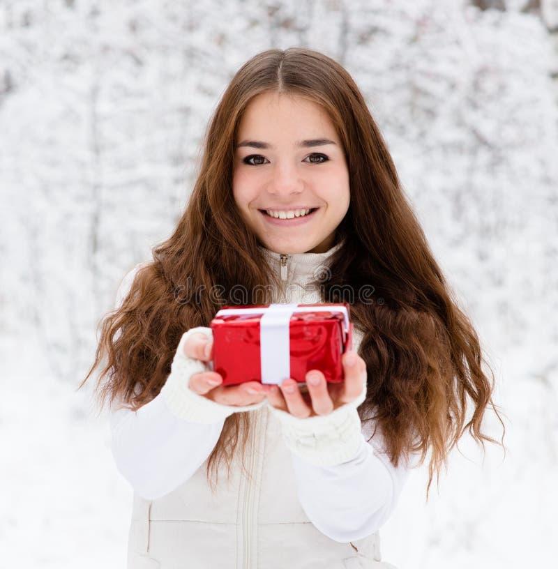 有站立在冬天森林里的小红色礼物盒的女孩 库存照片