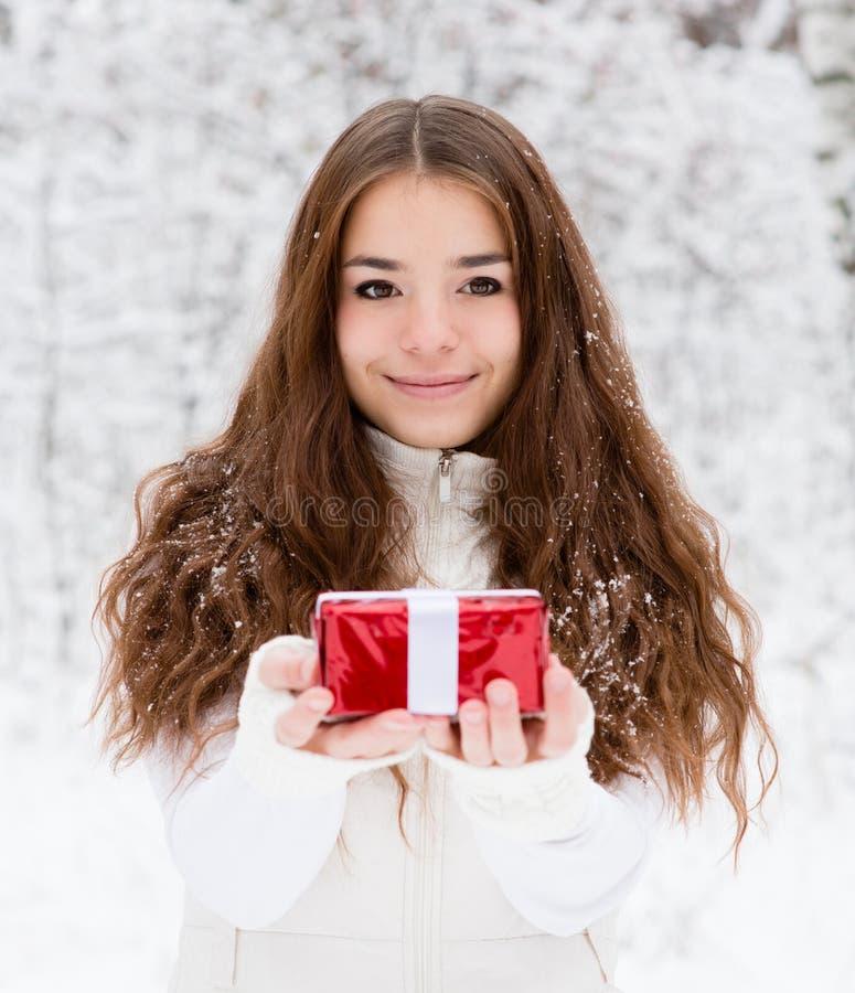 有站立在冬天森林里的小红色礼物盒的女孩 免版税图库摄影