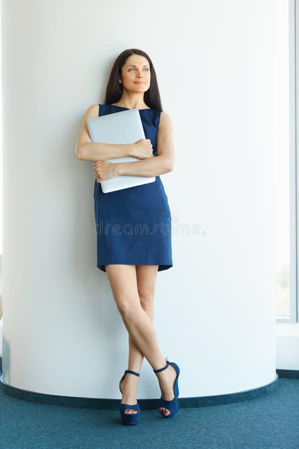 有站立在办公室的便携式计算机的女实业家 Busi 图库摄影