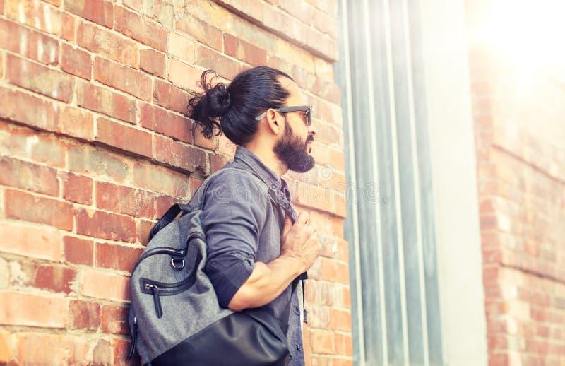 有站立在城市街道墙壁的背包的人 免版税库存图片