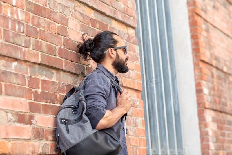 有站立在城市街道墙壁的背包的人 库存照片