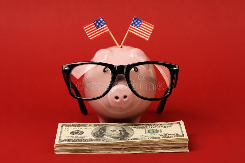 有站立在堆金钱美国人一百元钞票的玻璃和两面小美国旗子黑双孔构架的存钱罐  免版税库存照片