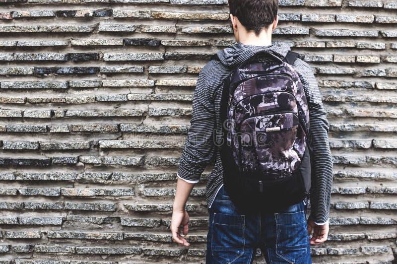 有站立在墙壁附近的背包的少年 免版税库存照片