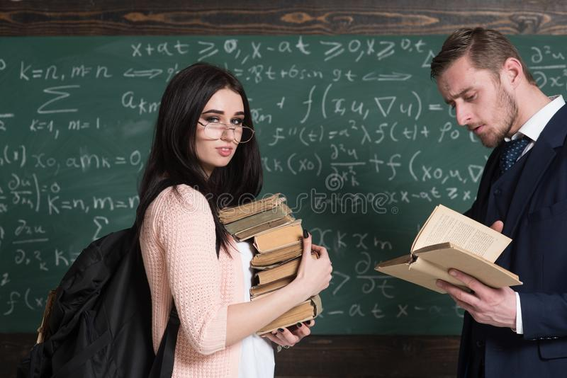 有站立在她时髦的年轻教授前面的书堆的微笑的女孩集中了读书 免版税库存照片