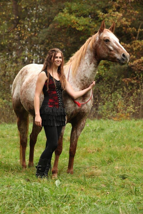 有站立在好的马旁边的好衣服的美丽的女孩 图库摄影