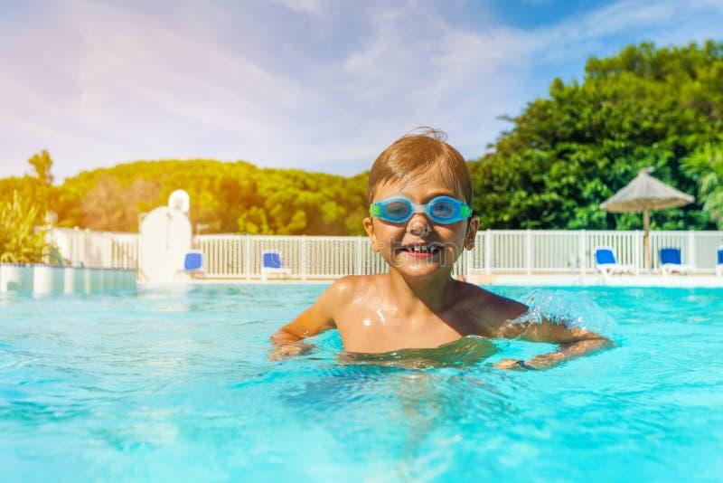 有站立在室外水池的游泳风镜的男孩 免版税图库摄影