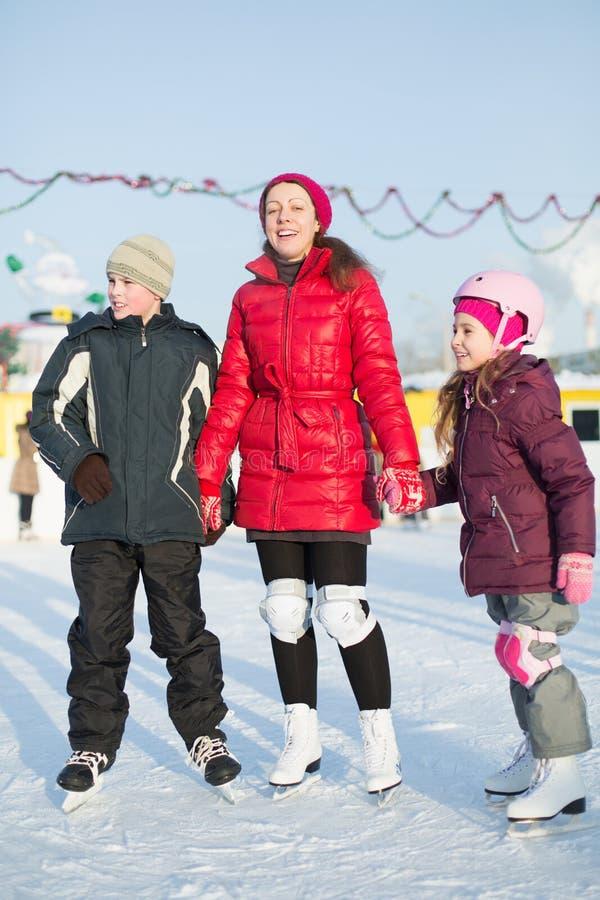 有站立在室外滑冰场的孩子的一个母亲 免版税库存图片