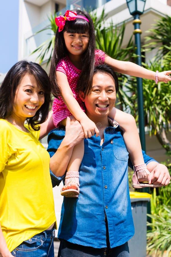 有站立在家前面的孩子的亚洲家庭 免版税库存照片