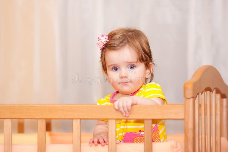有站立在小儿床的簪子的小孩子 库存照片