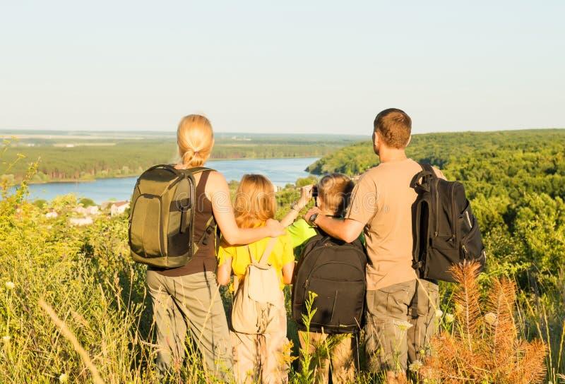 有站立在小山和看的两个孩子的愉快的家庭 免版税库存图片