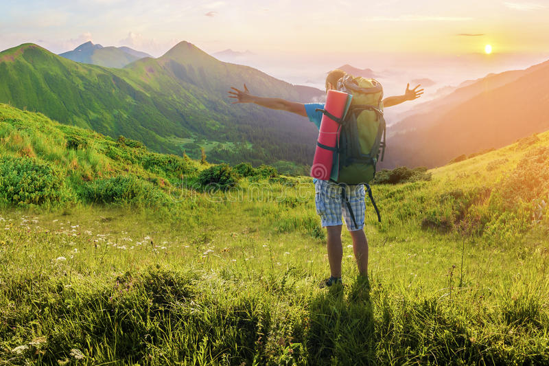 有站立在山的背包的远足者 惊人的自然土地 免版税库存图片