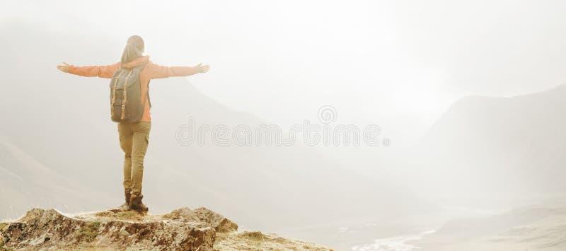 有站立在山的被举的胳膊的徒步旅行者女孩 库存图片