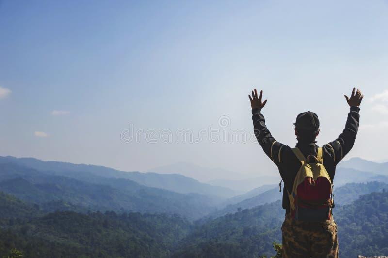 有站立在山顶部的背包的年轻人徒步旅行者 免版税图库摄影
