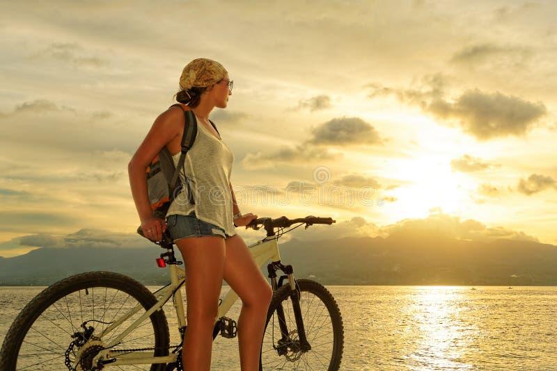 有站立在岸的背包的少妇在他的自行车附近 免版税库存照片