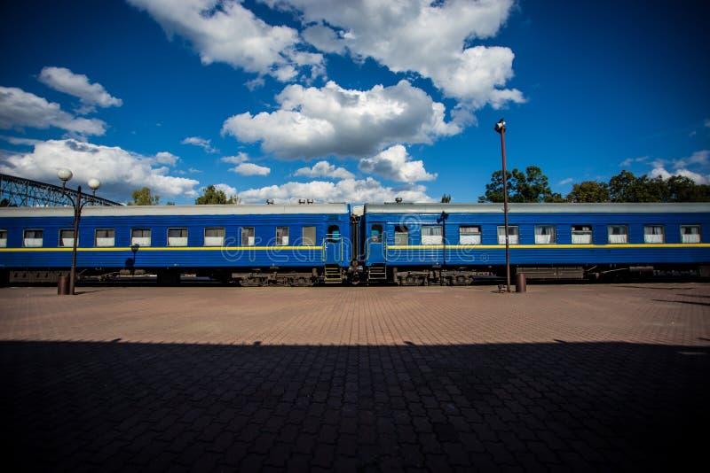 有站立在平台的蓝色无盖货车的火车反对美丽的天空背景  免版税库存照片