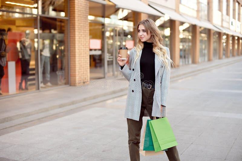 有站立在店面在街道上的商店窗口附近的购物带来的逗人喜爱的年轻时尚妇女户外 库存照片