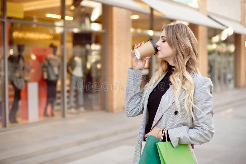 有站立在店面在街道上的商店窗口附近的购物带来的逗人喜爱的年轻时尚妇女户外 图库摄影