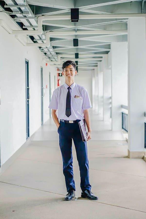 有站立在教室前面的制服的年轻学生 免版税库存照片