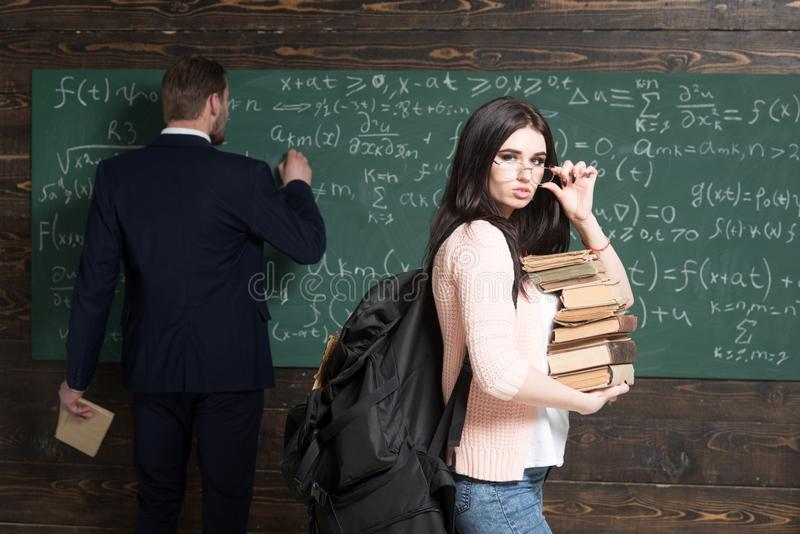 有站立在教室的堆的深色的学生书,当教授在绿色委员会时写着惯例 免版税库存图片