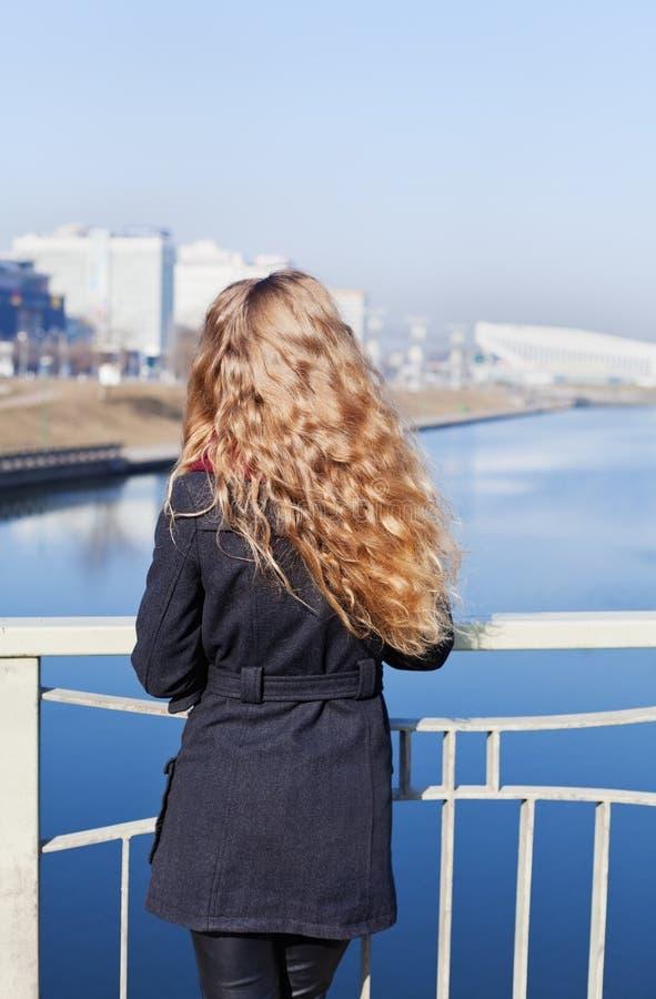 有站立在桥梁和看河和城市的长的卷发的年轻白肤金发的式样女孩在大风天 免版税图库摄影