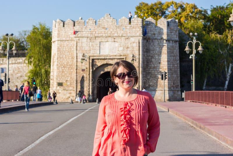 有站立在桥梁的太阳镜的年轻女人在街道和微笑中间 免版税库存图片