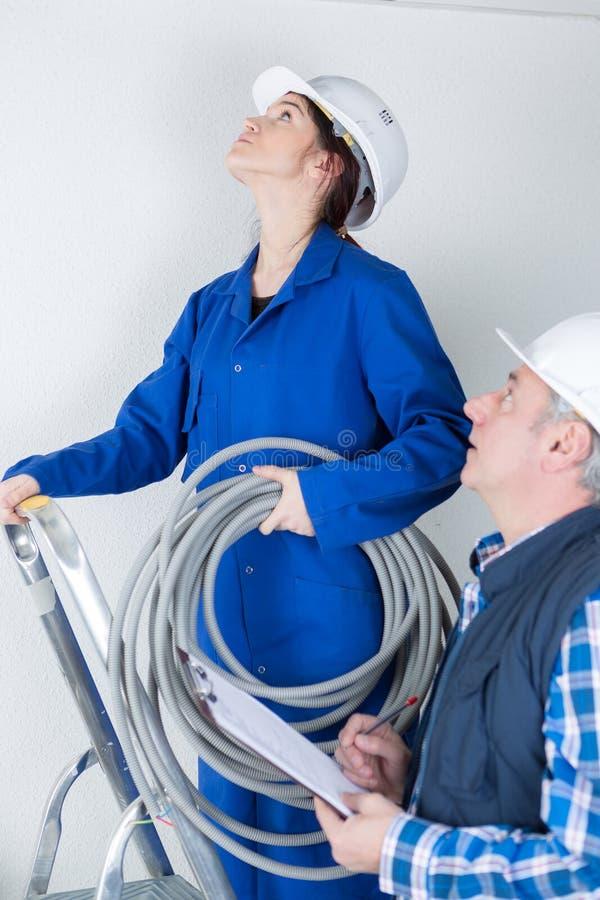 有站立在梯子的辅导者的年轻女性电工 免版税库存照片