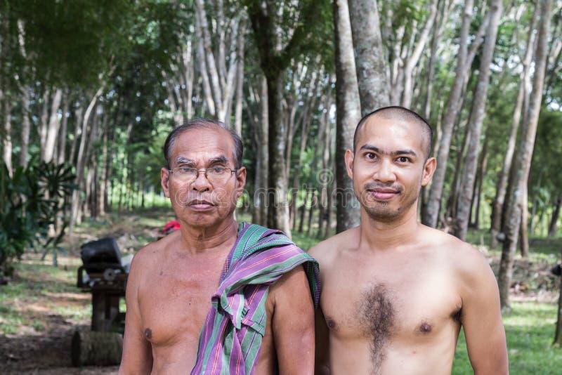 有站立在橡胶树庭院里的儿子的泰国年迈的花匠人 免版税库存照片