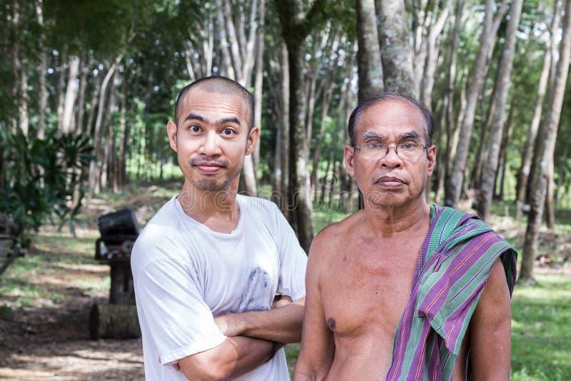 有站立在橡胶树庭院里的儿子的泰国年迈的花匠人 库存照片