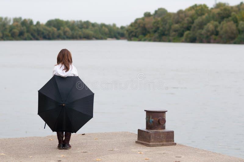 有站立在河船坞的伞的孤独的十几岁的女孩在秋天 免版税库存照片