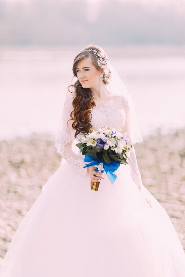 有站立在海滩的时髦的花束的美丽的美妙的卷曲新娘 免版税库存照片