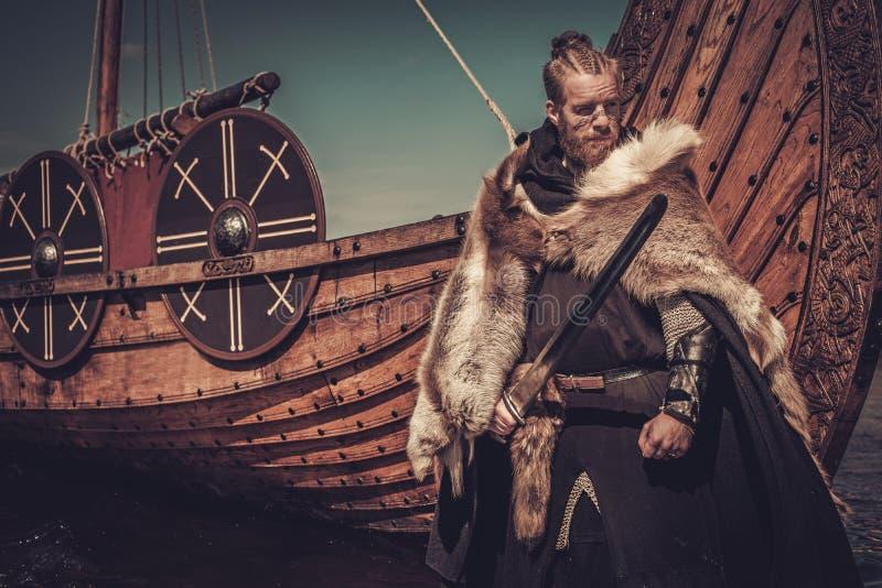 有站立在海滨的Drakkar附近的剑的北欧海盗战士 免版税库存照片
