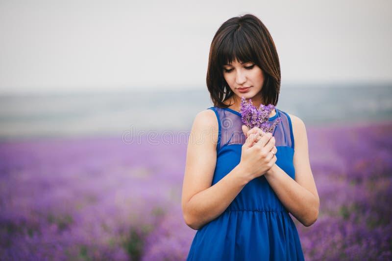 有站立在淡紫色领域的淡紫色花束的妇女 库存图片