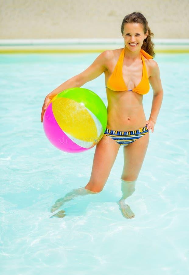 有站立在游泳池的球的妇女 免版税库存照片