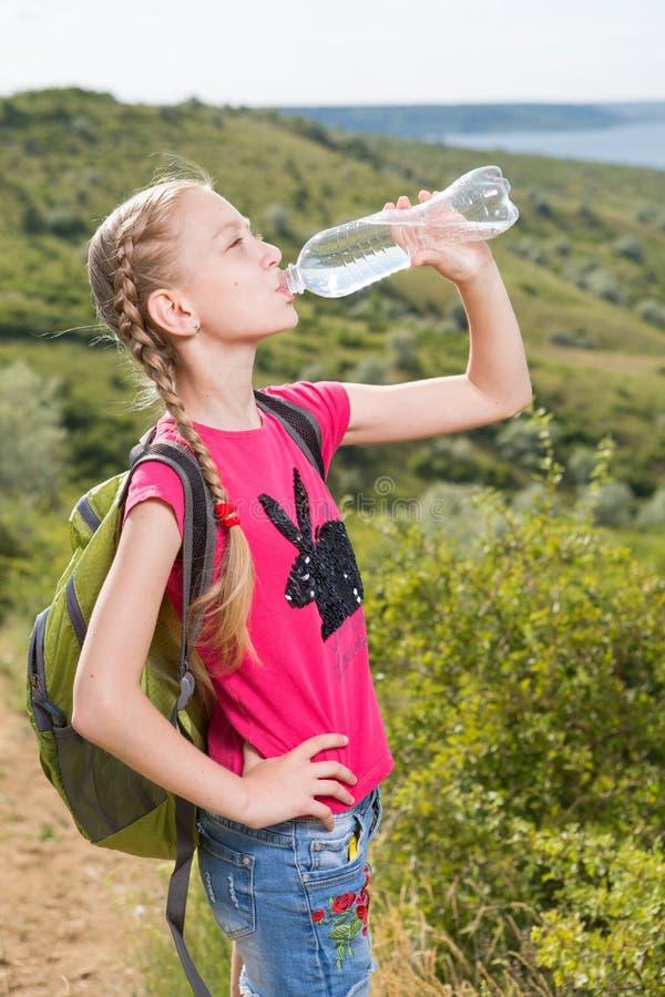 有站立在湖和饮用水的背景的背包的女孩 免版税库存图片