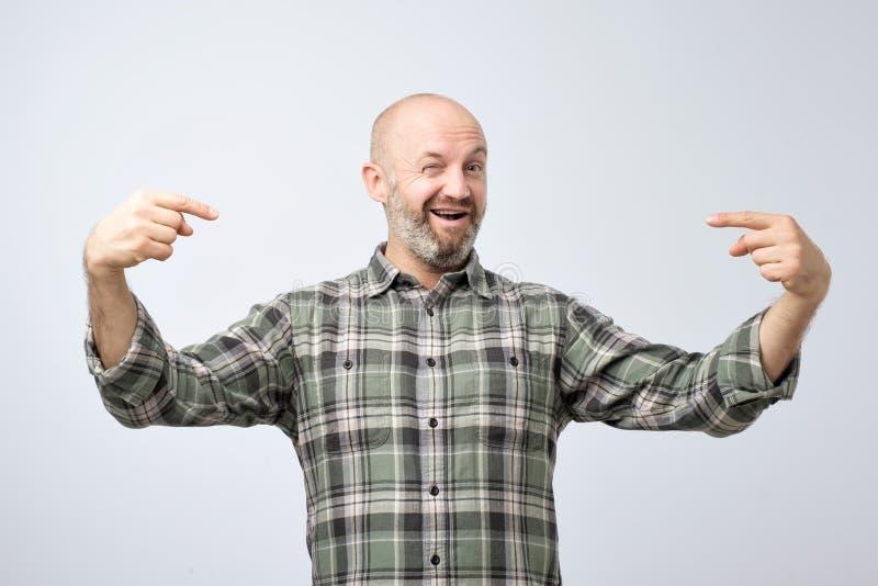 有站立在灰色难看的东西墙壁的胡子的成熟秃头成人人看起来确信与在面孔的微笑 免版税图库摄影