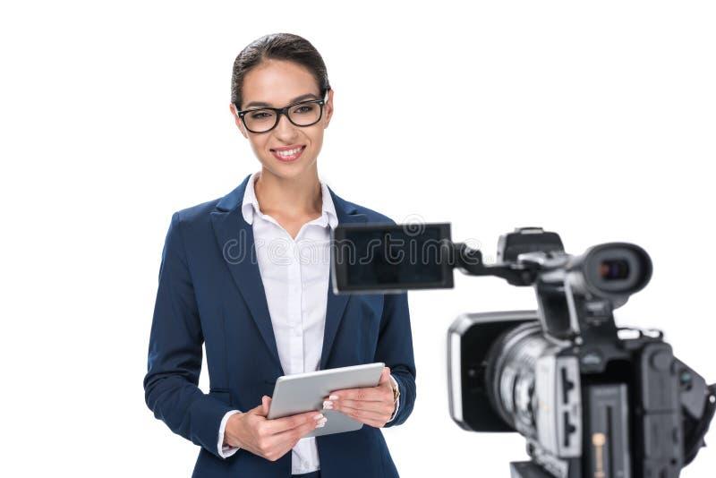 有站立在照相机前面的数字式片剂的可爱的女性新闻广播员, 免版税库存图片