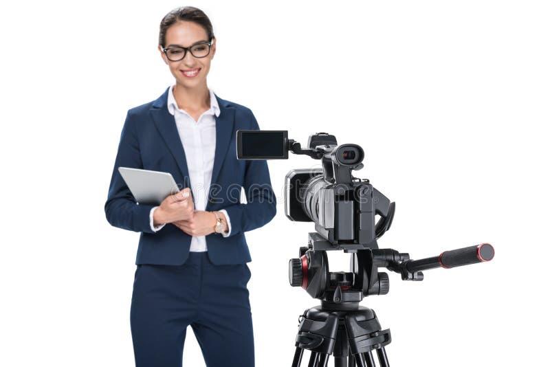 有站立在照相机前面的数字式片剂的微笑的女性新闻广播员, 库存图片