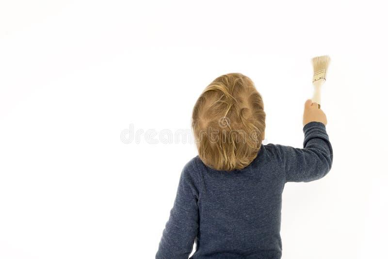 有站立在白色墙壁附近的画笔的男婴 库存照片