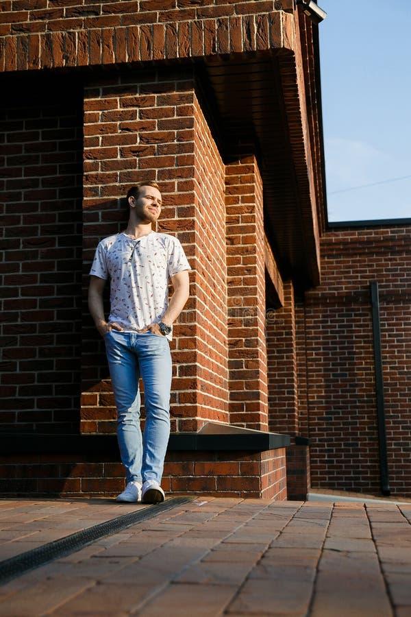 有站立在砖墙的刺毛的年轻美丽的时髦的人在一个夏天晚上 库存照片