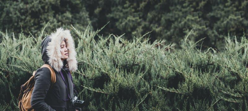 有站立在绿色杉木冷杉森林的毛皮的亚洲女服外套 免版税库存照片
