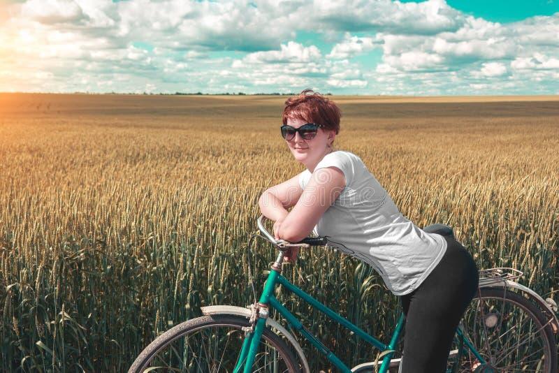 有站立在老自行车附近的姜头发的逗人喜爱的女孩 俏丽的妇女和葡萄酒在金黄麦田中骑自行车在晴朗的summ 免版税库存图片
