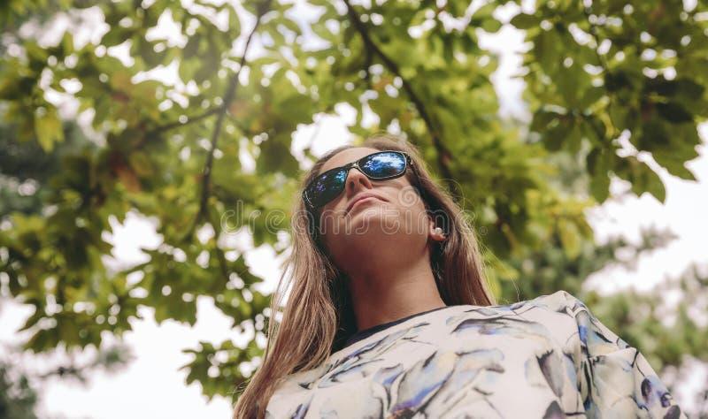 有站立在自然背景的太阳镜的妇女 免版税库存图片