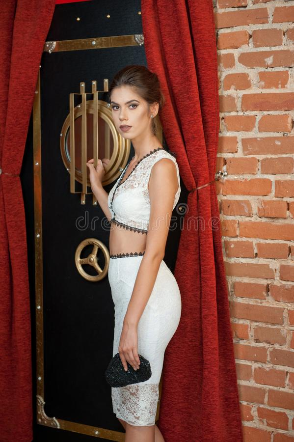 有站立在葡萄酒场面的一个保险柜附近的白色礼服的时兴的肉欲的可爱的夫人 深色的头发短小妇女 免版税库存图片